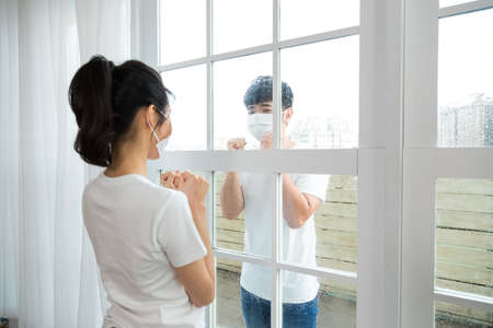 Man visiting girlfriend quarantined in home. And couple showing power gesture to each other.