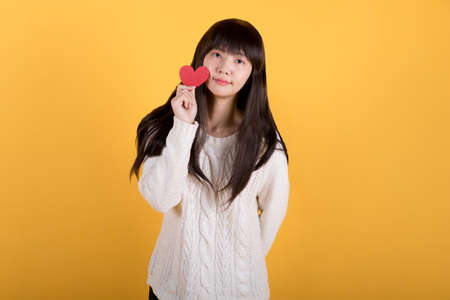 Portrait of lovely asian woman in white sweater holding a gift. valentine's day concept photos. Studio shot isolated on yellow background. 免版税图像