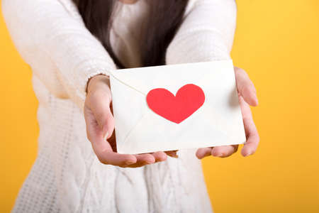 Close up of hand. Woman holding valentine's day greeting card. studio shot isolated on yellow background.