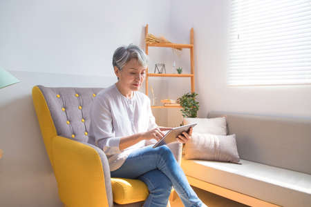 Senior woman sitting on sofa and drinking coffee next to the window.