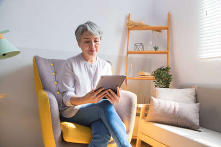 Senior woman holding a cup of coffee or tea relaxing at home in the morning. Stock fotó