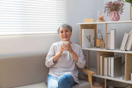 Senior woman holding a cup of coffee or tea relaxing at home in the morning. 免版税图像