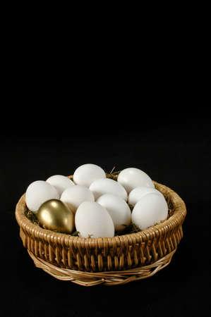 Basket with golden egg among white eggs