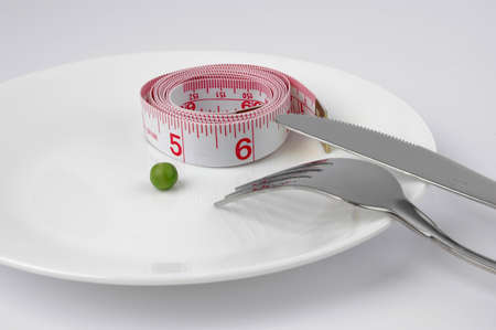starvation: Meauring Tape and pea on a plate diet