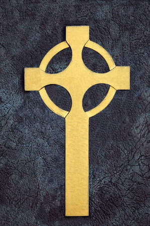 Golden Celtic Cross over stone surface photo