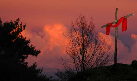 redemption of the world: Cross with red linen on a sunset background