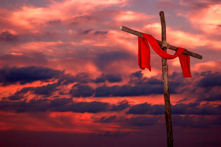 redemption: Cross and red tunic on a colorful sunset Stock Photo