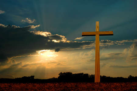 Wooden cross over sunset background. photo