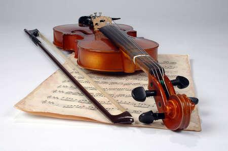 Old violin and vintage music sheet make an elegant still life. photo