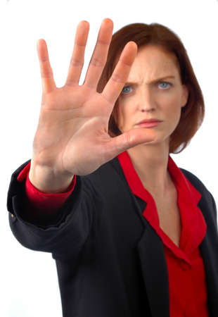Young woman showing hand to stop unwanted action.