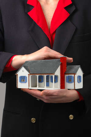 Woman holding house representing home ownership and the Real Estate business photo