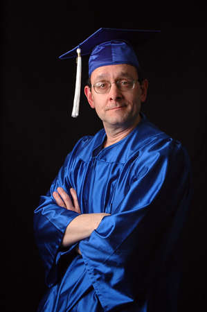 doctorate: Portrait of man with graduation gown and cap over a black background.