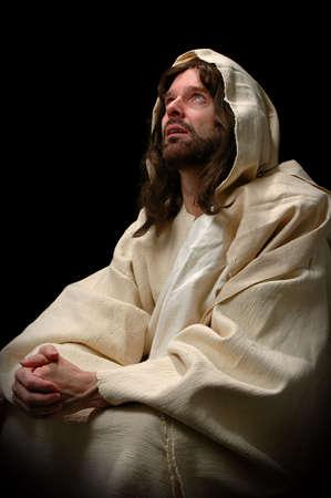 son of god: Jesus in prayer over a dark background Stock Photo