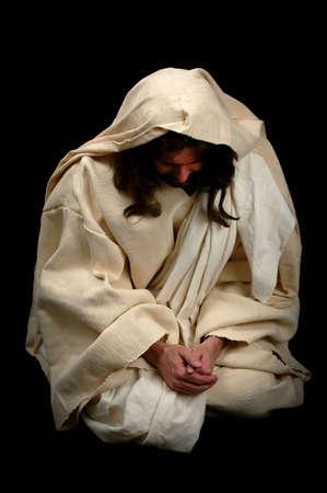 personas orando: Jes�s orando de rodillas sobre un fondo negro