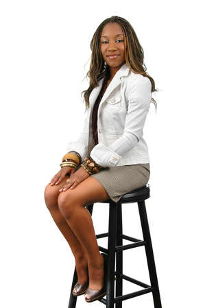 Young African American woman sitting on stool.