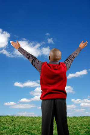 Boy with arms raised expressing joy over a blue sky with clouds.
