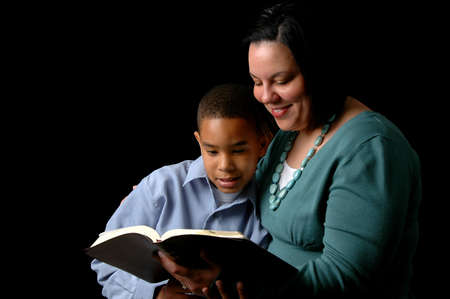 kids reading: Mother reading the Bible to young son over a black background