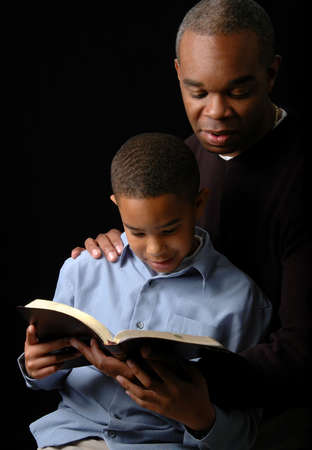 kid reading: Father and son reading a Bible over a black background.