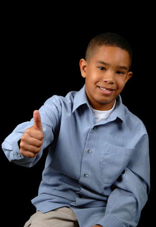 Young boy showing the thumbs-up over a black background. photo