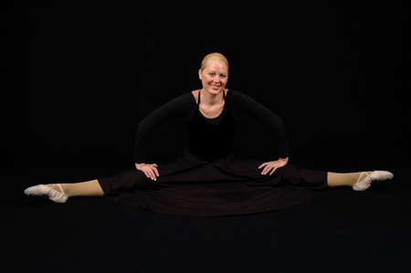 stratching: Ballerina stratching dressed in black outfit over a dark background.