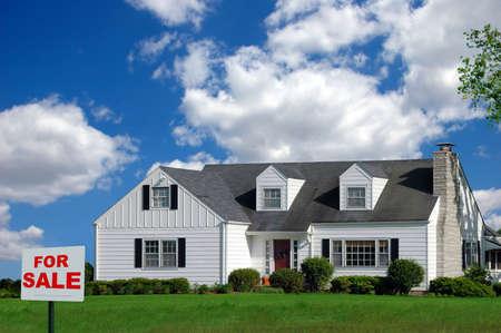 Huis met Te Koop bord aan de voorkant werf over een kleurrijke hemel met wolken. Stockfoto