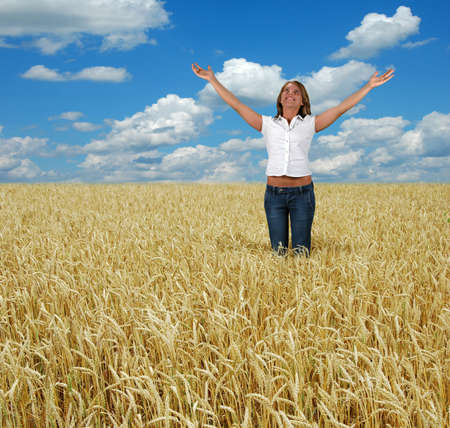 wheatfield: Young woman with arms stretched toward heaven in a wheatfield. Stock Photo