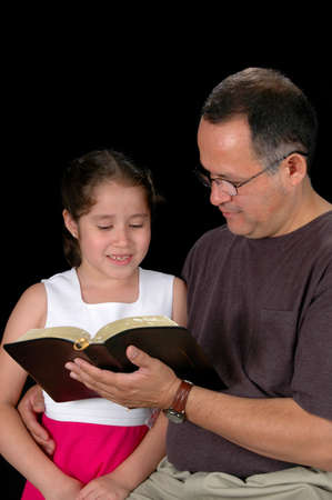 fatherhood: Latino father and daughter reading a Bible isolated over a black backround. Stock Photo