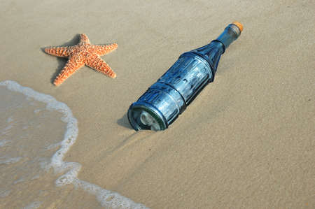 Starfish and message ina vintage bottle on the shore photo