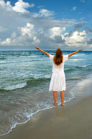 Beautiful woman with arms fully open expressing gratitude on the shore