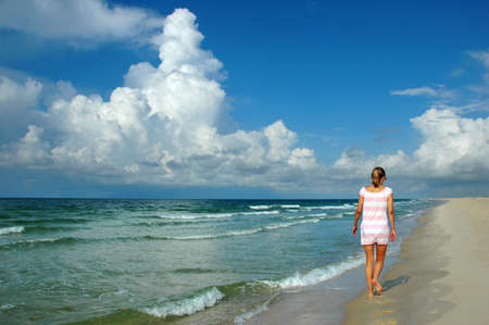 Young Woman walking on beach with cumulous clouds and water in the background.