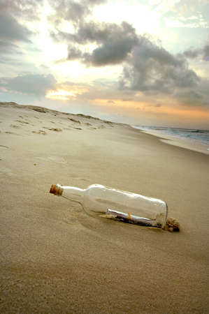 corked: Message in a bottle stranded on a deserted shore as the sun is setting Stock Photo