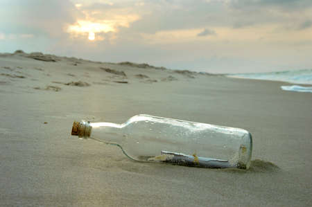 castaway: Message ina bottle washed on shore during a sunset Stock Photo
