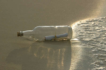 castaway: Message in a bottle with strong sunlight at sunset Stock Photo