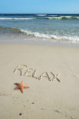 Relax written on the shore and starfish on the sand photo