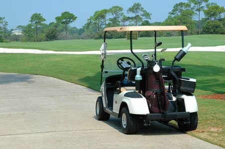 Golf kar op de weg van de golfbaan