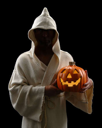 ugliness: Hooded man holding jack-o-lantern isolated over a black background Stock Photo