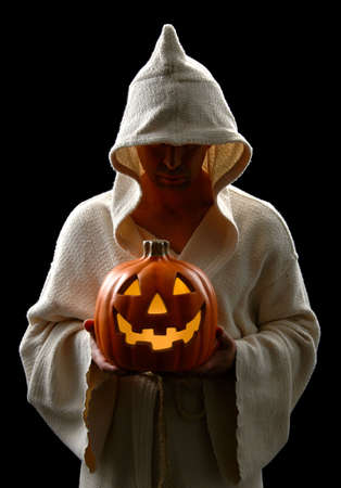 ugliness: Hooded man holding a Jack-0-Lantern isolated over a black background.