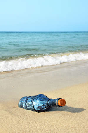 castaway: Message ina bottle in a vintage blue bottle on the shore Stock Photo
