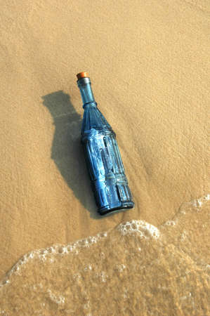 castaway: Message in a vintage blue bottle on a sandy shore Stock Photo