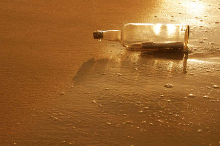 castaway: Message in a bottle on a sandy shore at sunset