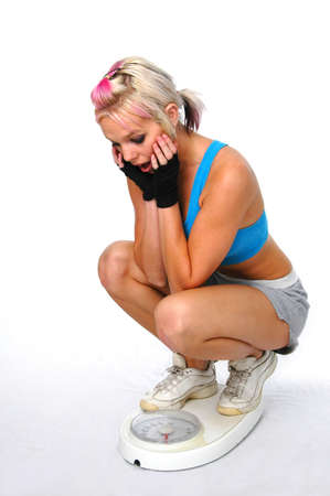 nourish: Beautiful woman in fitness outfit being surprised by weight on scale. Stock Photo