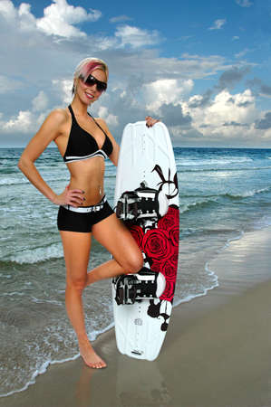 sensational: Beautiful girl with wakeboard on the shore of beach 스톡 사진