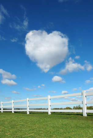 Heart cloud in the sky with white fence in the foreground. Stock Photo - 2654844