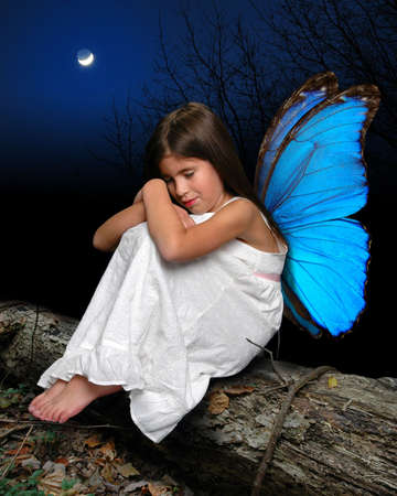 angel tree: Little fairy girl with blue wings sitting on tree trunk with moonlight as background Stock Photo