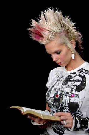 punk hair: Punk girl reading the Bible isolated over a black background.