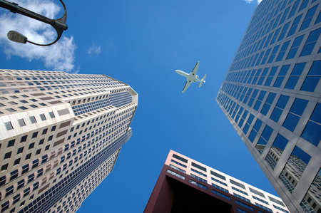 buildings: Corporate jet flying high above business district.