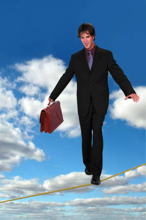 Busimessman confidently walking on tight rope holding a briefcase over a sky background. photo