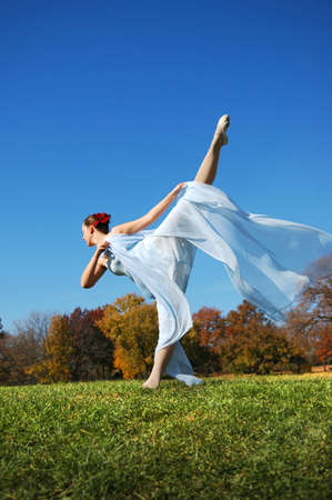 Ballerina performing outdoors during a sunny day.