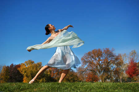 grace: Beautiful ballerina dancing outdoors on a sunny day.