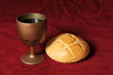 bread and wine: Elementos de comuni�n, representados por el pan y el vino, sobre un fondo rojo  Foto de archivo